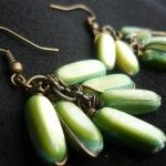 Orecchini realizzati con perle a forma di chicco di color verde e sfumate al centro e creati con una finitura in bronzo.