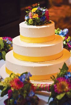 White chocolate wedding cake, by Windows Catering, decorated with yellow gingham ribbon and fresh flowers.   Photo by Holland Photo Arts
