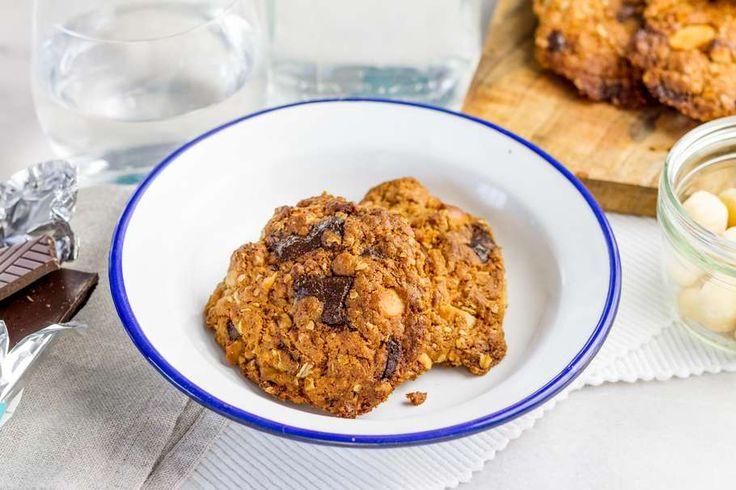 Recept voor macadamia-chocoladekoeken voor 4 personen. Met bakpapier, macadamianoten, pure chocolade, bloem, boter, suiker, ei en havermout
