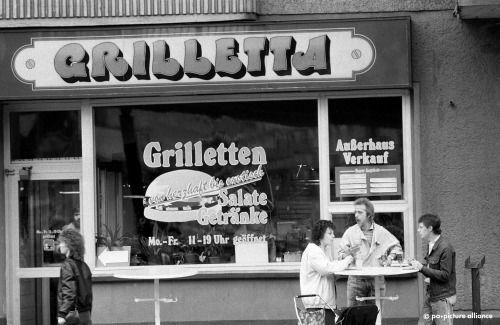 BERLIN 1990, im Frühjahr nach dem Mauerfall. Die DDR kreierte ihre eigene Sprache. Nicht Burger, sondern Grilletten heißt das Fast-Food (und Hähnchen heißen 'Breuler') an der Schönhauser Allee in Prenzlauer Berg.
