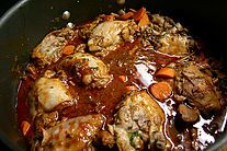 Coq au vin is a French dish of chicken braised with wine, lardons, mushrooms, and optionally garlic.