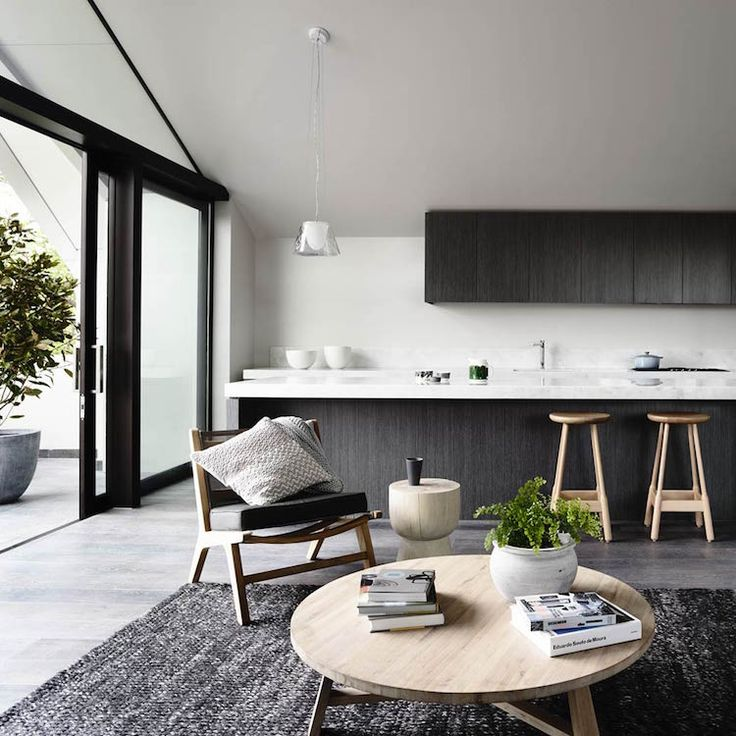 dark wood cabinetry + light wood floor + vaulted ceiling + warm wood tones + minimal