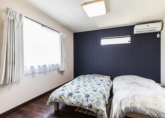 ネイビーのアクセントクロスと濃いブラウンの床でシックな印象の寝室に