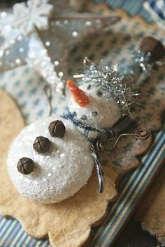 She made the little tiny snowman out of small styrofoam balls cut in half then used gesso, white paint, glitter to color him. His nose is made out of oven baked clay. So CUTE!