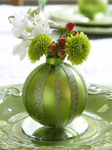 Cute idea for place setting on your holiday table. Use a festive oversize ornament, glue to a small mirror or piece of glass, remove the cap and fill with artificial or natural greenery and floral items.