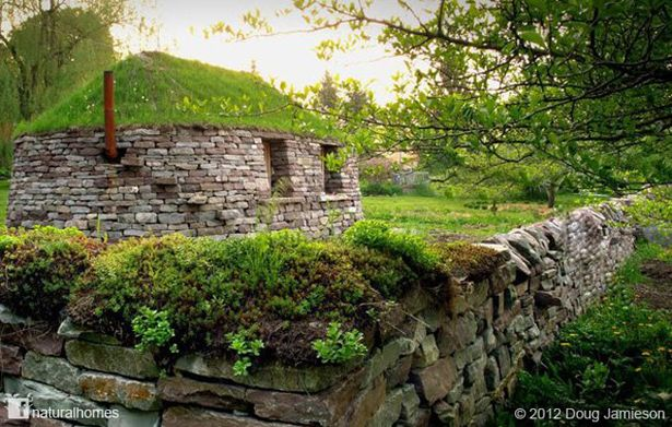 This is a traditional Scottish dry stone home called a Blackhouse however it's in Canada. Here are some in blackhouses in Scotland. The house was built using 126 tons of stone at Eric Landman's farm near Grand Valley, ON. Notice steps are built in to the wall leading up to the chimney and the green roof. More at www.naturalhomes.org/timeline.htm