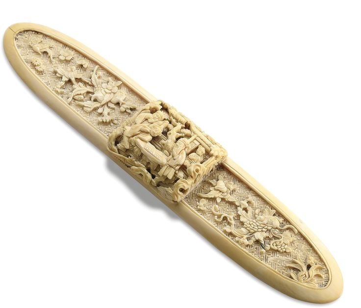 A CARVED IVORY SCROLL WEIGHT OR SILK SPINDLE QING DYNASTY, 18TH / 19TH CENTURY of oblong section, the raised centre finely carved in high relief with two scholars engaged in a game of weiqi, the sides detailed with detached sprays of leafy pomegranate and squirrel and grapes, all reserved on a leiwen ground, the ivory bearing a fine age patina