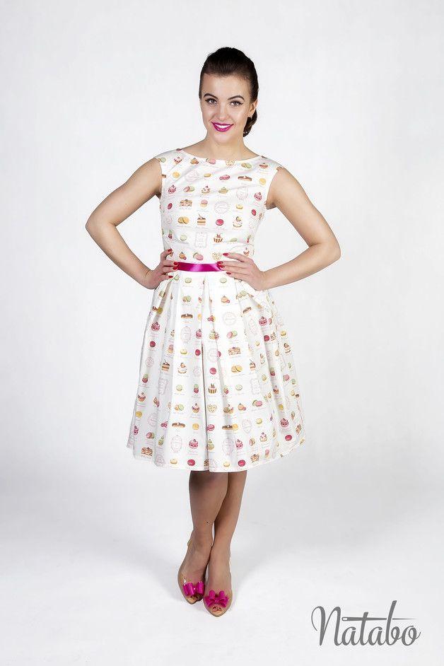 Bawełniana sukienka w słodycze. Sukienka jest uszyta z bawełnianej tkaniny wysokiej jakości w kolorze naturalnej bieli z nadrukiem babeczek, makaroników, eklerów i innych słodkości. Góra z...