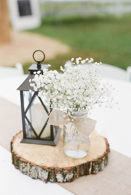 Brides.com: . A wooden stump, mason jar of baby's breath, and classic lantern incorporate the neutral look in its more natural forms, making for a bucolic inspired centerpiece.