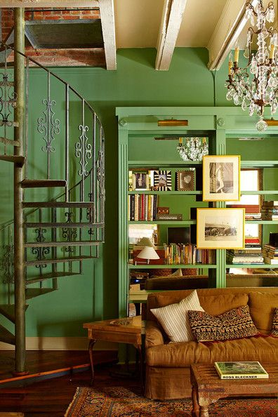 A green library and living room with built-in mirrored bookcases and a spiral staircase in a historic New Orleans home.