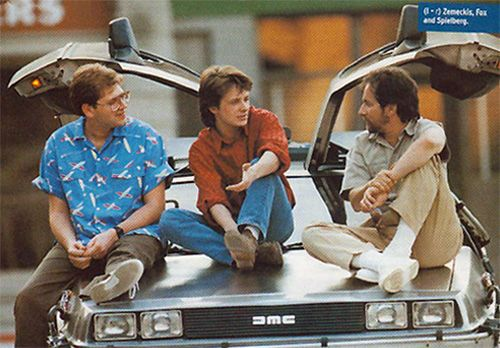 Robert Zemeckis, Michael J Fox and Steven Spielberg having a chat on the hood of the DeLoreon from Back to the Future.