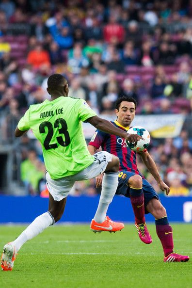 Raoul Cedric Loe (L) of CA Osasuna and Xavi Hernandez of FC Barcelona fight for the ball during the La Liga match between FC Barcelona and CA Osasuna at Camp Nou on March 16, 2014 in Barcelona, Catalonia.