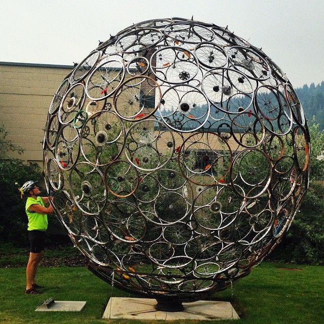A cyclist admires this great outdoor sculpture composed of bicycle wheels in Castlegar, BC.
