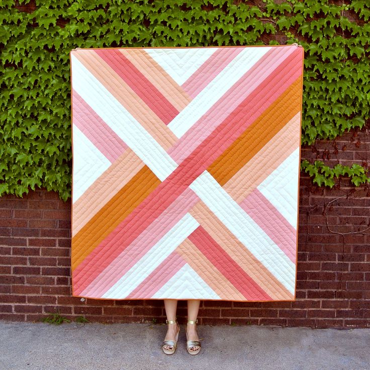 The Maypole quilt pattern is a simple yet bold design reminiscent of ribbons woven together. This striking composition varies greatly based on color.