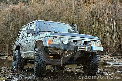 Jeep standing on small river with rocks agaisnt woods