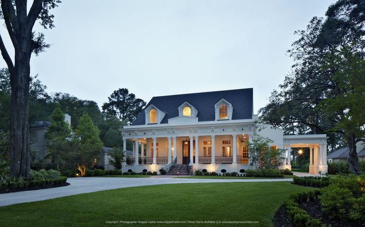 Front entry at dusk with cozy porch and white columns on New Orleans-inspired home. Designed by Kevin Harris Architect LLC. Photographed by Chipper Hatter. #southern #architecture #nola