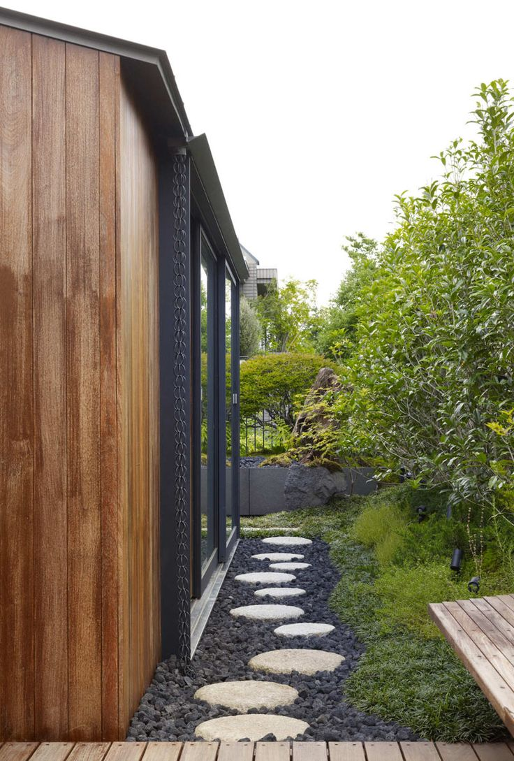 14 Modern Homes That Use Rain Chains To Divert Water | This rain chain, made from a traditional chain, is hidden next to the extended window frame on the side of this house and guides water in between the rocks of the footpath.