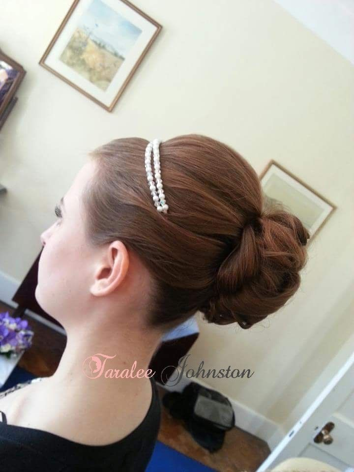 A smooth bun with detail, a classic bridal style.