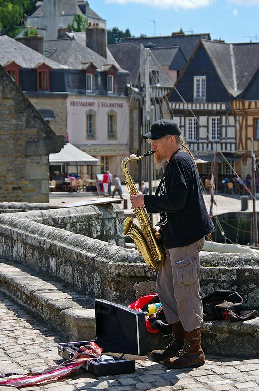 Un joueur de saxophone sur le vieux pont de Saint-Goustan à Auray. En arrière plan, les jolies maisons à colombages de la place Saint-Sauveur. A saxophone player on the old bridge of Saint-Goustan a small Harbour in South Brittany, France.