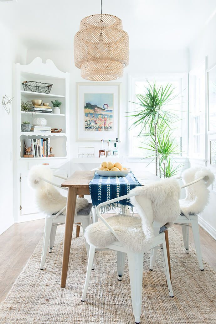 Beachy dining space with an IKEA pendant light, white metal chairs, and lamb throws