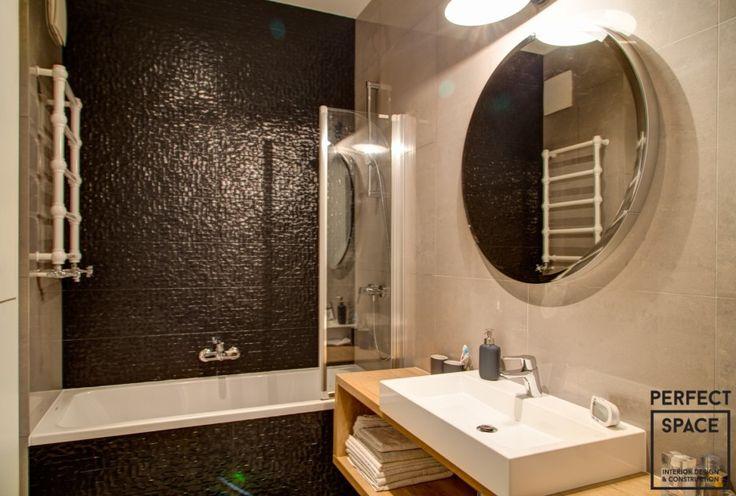 Łazienka urządzona w nowoczesnym stylu z czarnymi połyskującymi płytkami tuż nad wanną. Kaloryfer łazienkowy o oryginalnym kształcie dodaje stylu.