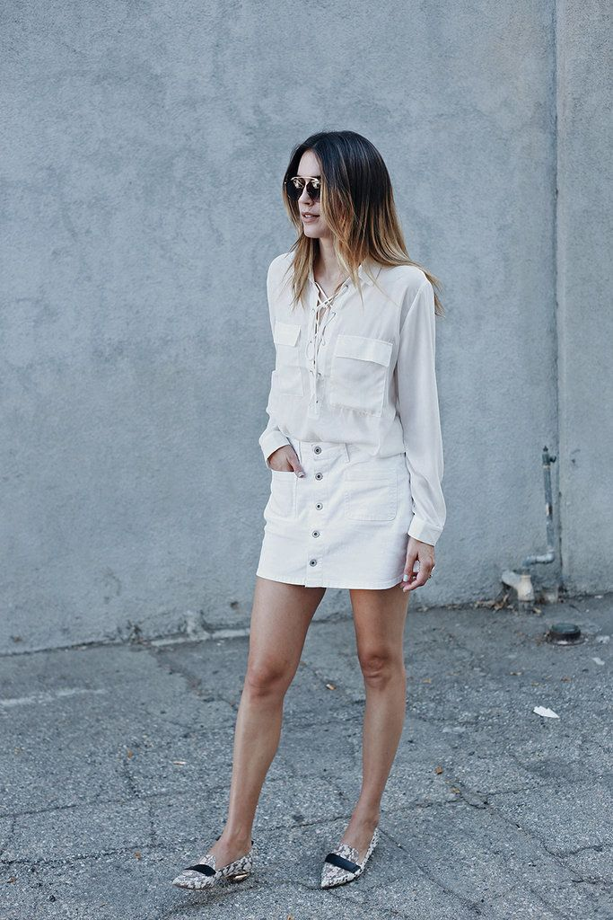 A lace-up top tucked into a buttoned mini skirt with pointy-toe flats