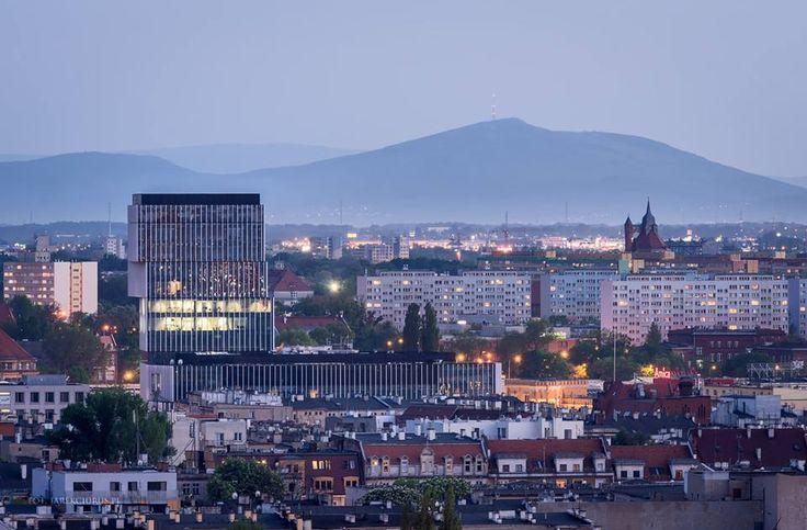 Widok na Wrocław. Po lewej stronie - Silver Tower Center, a po prawej zabytkowa wieża ciśnień przy Al. Wiśniowej. W tle majestatycznie wznosi się Ślęża. Z Fotografia Architektury Maciej Lulko i Janusz