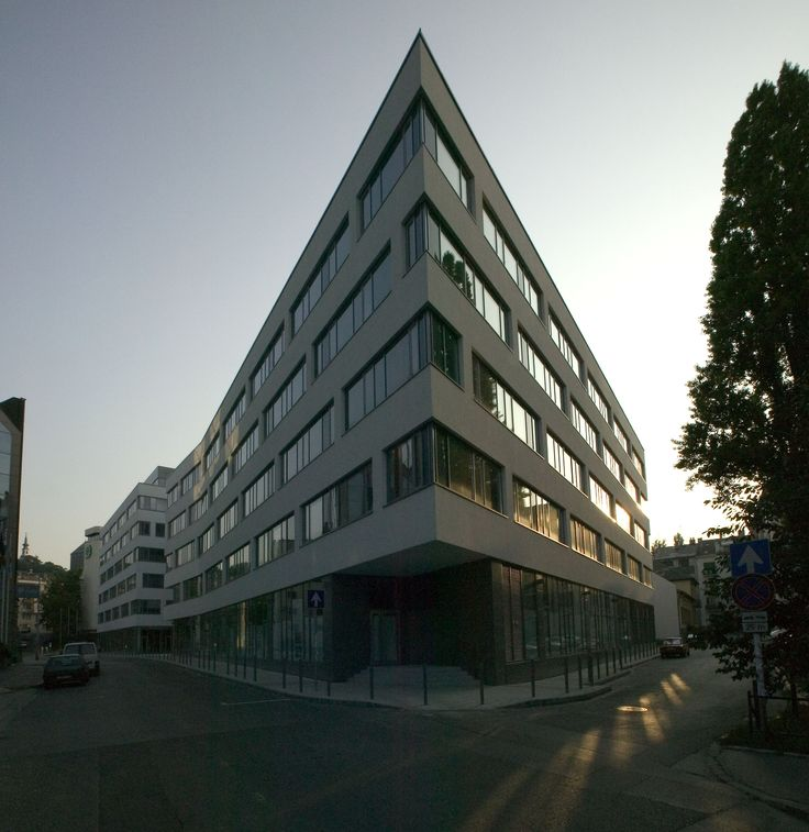 Office Building, Viziváros by Földes Architects. Windows shining as the sun goes down