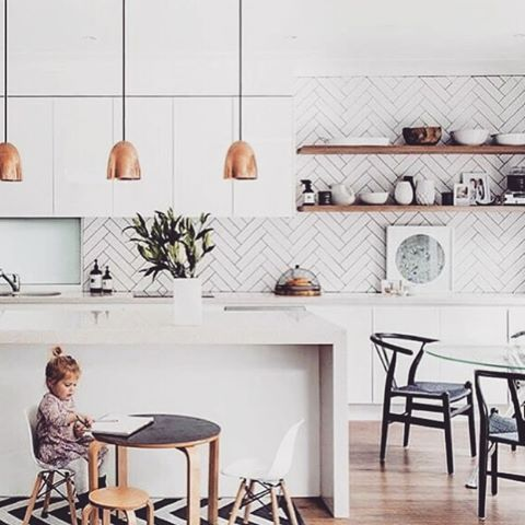 Thursday morning kitchen inspo! It's no secret I love a great feature tiled splash back and open shelves in a kitchen. And how amazing does this herringbone pattern look? Using a darker grout makes the pattern appear prominent, and the copper pendants are just perfect here. This cool kitchen belongs to fashion stylist @kristinrawson and was featured in @adoremagazine earlier this year. Styling by @peepmystyle  and 📷 by @hannahblackmore ☀️