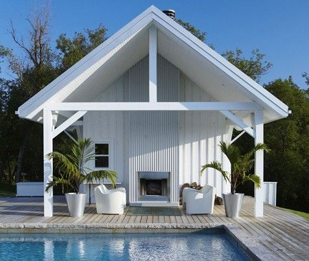 Wood decking frames the pool like a boardwalk, and fiberglass sofas add a glam note.