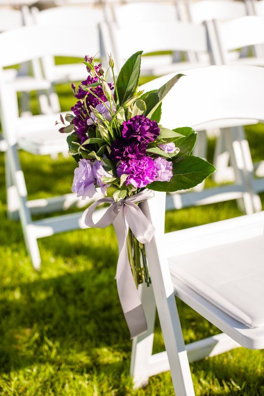 pew marker clusters of purple stock, purple lisianthus, carnations, lemon leaf and variegated pitisporum are tied with grey ribbon for this outdoor wedding.