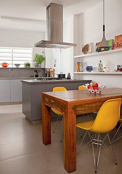 A cozinha do projeto da SAO Arquitetura tem ilha central e mesa de jantar. De madeira rústica, ela é acompanhada de cadeiras de design amarelas