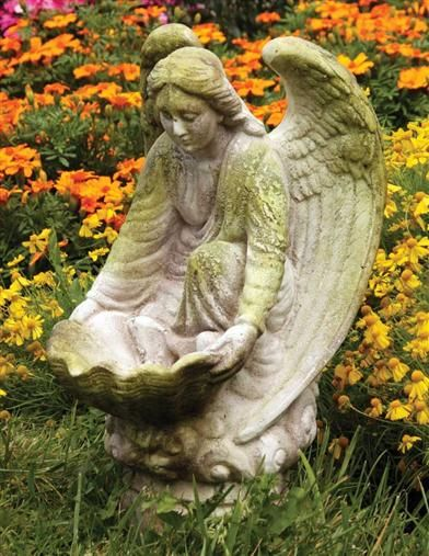 """Compassionate angel"" garden statue stands ready to provide food or water for birds or other small creatures."