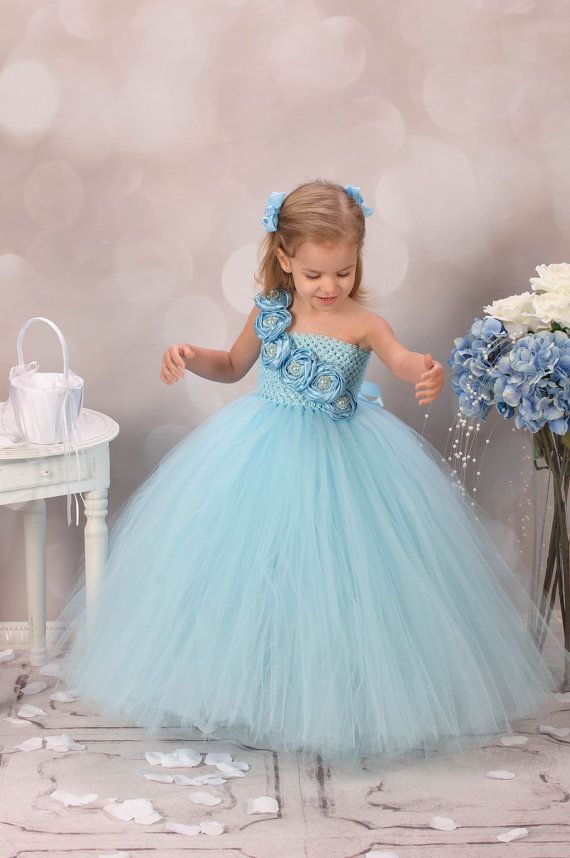 This is one of our couture line dresses! It is extremely full with hundreds of yard of premium quality tulle used. This dress can be customized in different color options, if interested in that, please send me a message.  It is made with a blue crochet top.  The front is embellished with blue satin rolled flowers. Each flower is accented with a rhinestone centerpiece.  The dress has a satin ribbon shoulder strap that is tied elegantly through the back.  The tulle is blue.  MEASUREMENT:  1)…