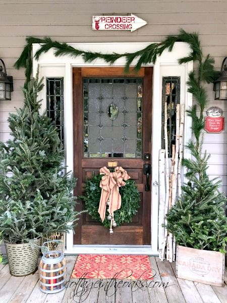 Christmas porch inspiration using lots of evergreens and birch logs!