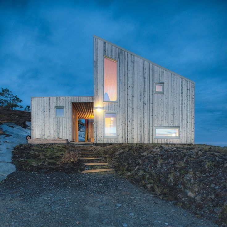 Designed by TYIN Tegnestue Architects, this wooden cabin is set among the marshland of coastal Norway and overlooks the ocean.