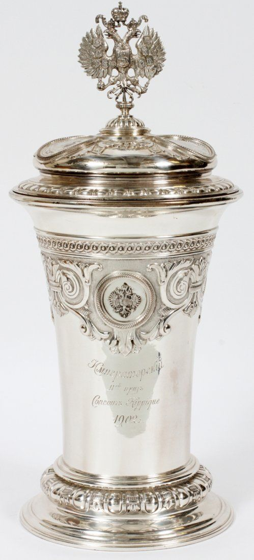 """RUSSIAN SILVER COVERED TROPHY CUP, K. FABERGE, DATED 1902, H 16"""", DIA 7"""", 'CONCOURS HIPPIQUE', ENCASED:A round trophy cup with tapering sides and flaring base surmounted by a domed cover centered with a crowned double-headed eagle finial; the cover and base are adorned with a total of six round medallions, five of which are portraits of royalty, the sixth a crowned double-headed eagle. Engraved inscription at the front of the cup includes """"Concours Hippique 1902"""". The cover is stamped at the…"""