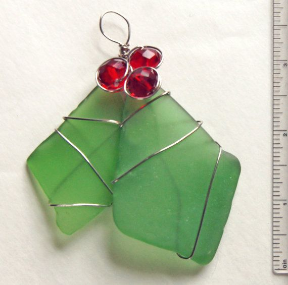 This unusual wire-wrapped sea glass Christmas ornament or suncatcher features two large shards of green sea glass, wire wrapped with three large red