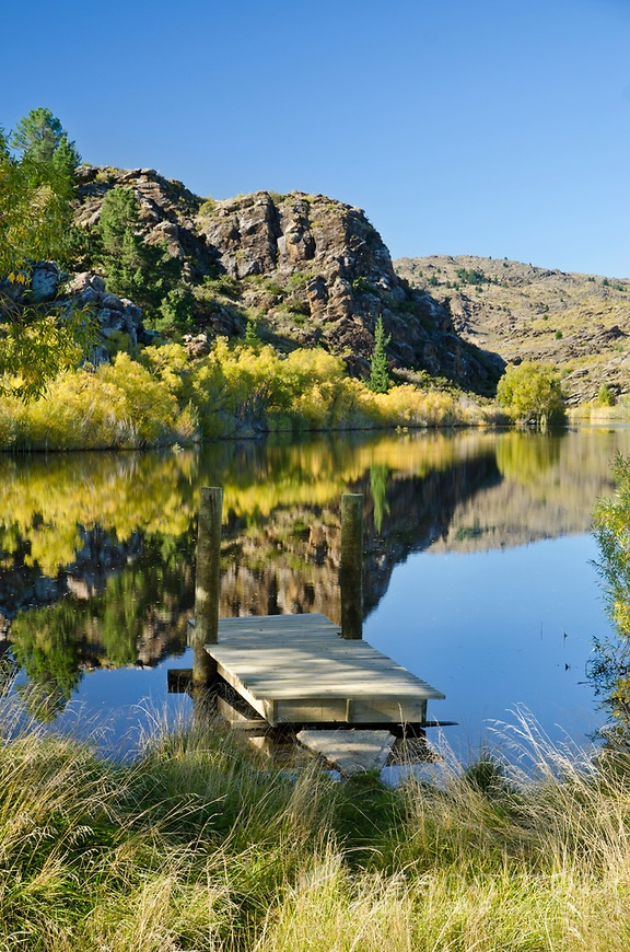 A calm Autumn day creates a perfect reflection in the water at Lower Manorburn Dam near Alexandra, Central Otago, South Island, New Zealand.