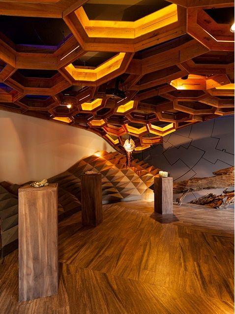Espacio Fa del Hotel NOI. Se utilizó terciado marino Rebest de 15 mm. cortado en forma geométrica, de acuerdo a la secuencia de Fibonacci. La madera se usó, además, en los tableros del cielo que asemejan un panel de abejas, en los plintos que soportan las esculturas y en una estructura semi circular que evoca la creación de la cultura.