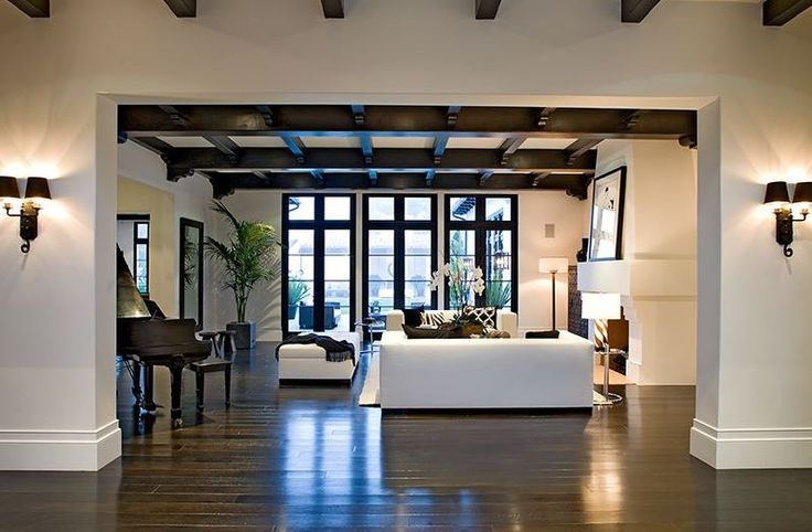 Foyer in a spanish revival home with painted black exposed beams and a view of the living room for Spanish colonial revival living room