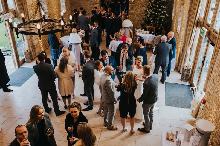 Balcony photo of the drinks reception area at @caswellhouse and festive decor for this Christmas wedding. Photo by Benjamin Stuart Photography #weddingphotography #caswellhouse #christmaswedding #weddingreception #weddingguests