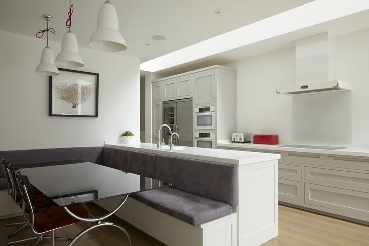 A clean and crisp handleless shaker design with Corian worktops and banquette seat. Miele appliances.