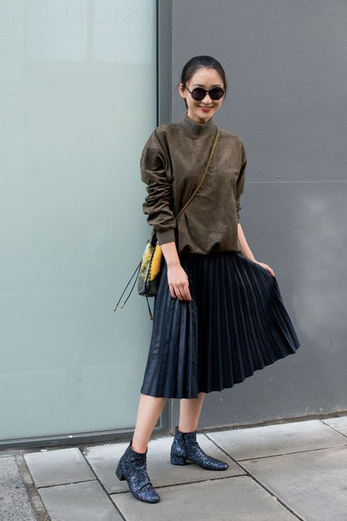 Black pleated skirt with a khaki sweater. and black letter boots. spotten on the Londen Fashion Week.
