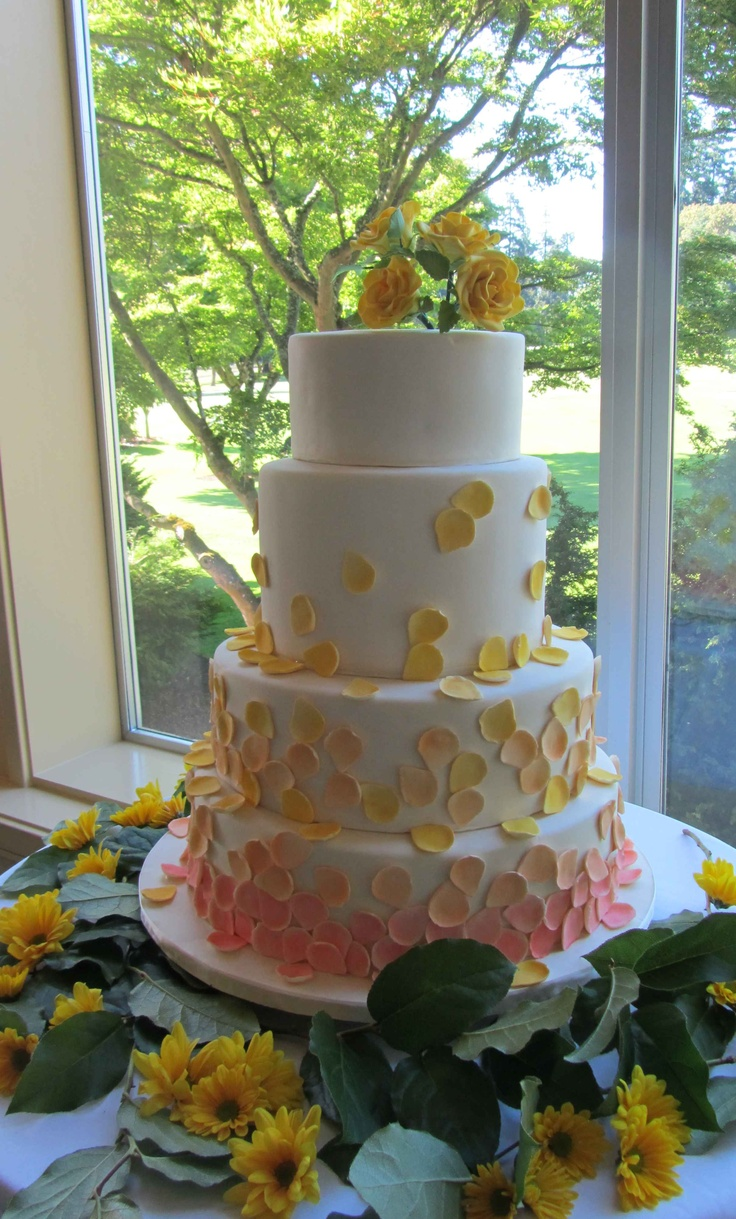 Four-tier wedding cake with cascading sugar rose petals in various shades of peach, salmon pink, and yellow. Handmade gumpaste roses adorn the top.