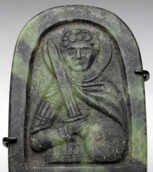 """Byzantine Greenstone Icon - Saint George. Byzantine Empire, Ca 900 - 1100 CE. Extremely rare, small greenstone """"icon"""" showing St. George, wearing a flowing cape, wielding a sword in his right hand shield in his left, halo surrounds his saintly head, Greek.This and more important Byzantine Art on CuratorsEye.com"""
