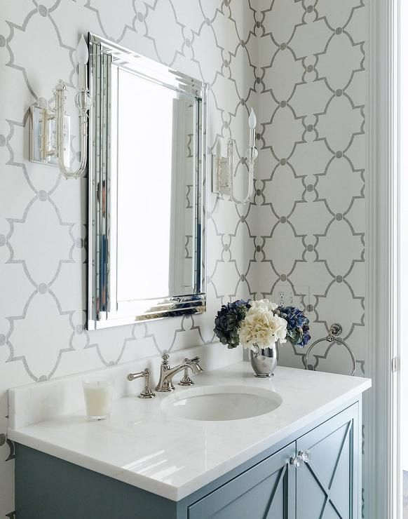 Chic bathroom features walls clad in gray quatrefoil wallpaper lined with a blue washstand fitted ...