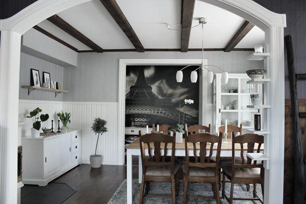 renoverat vardagsrum i vitt, grått och trärent. Inspiration vardagsrum i svart, vitt och grått. Parkett av trä panga panga. Trären hylla på väggen med prints i svart och vitt. Motiv med fjädrar på tavlorna. Tavlor svart och vitt. Bröstpanel i vitt. Möbler från EM möbler. Vitt vitrinskåp. Balkar i taket. Olivträd.