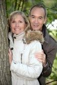 Mature couple out for an autumnal stroll in the woods stock photography