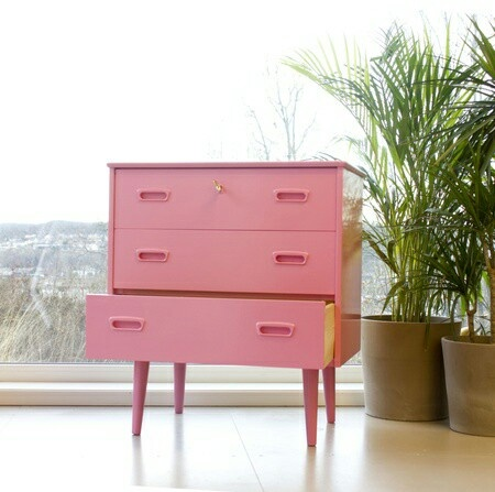 Redesigned, retro furniture: Teak dresser. Painted pink, inside there's yellow wallpaper.